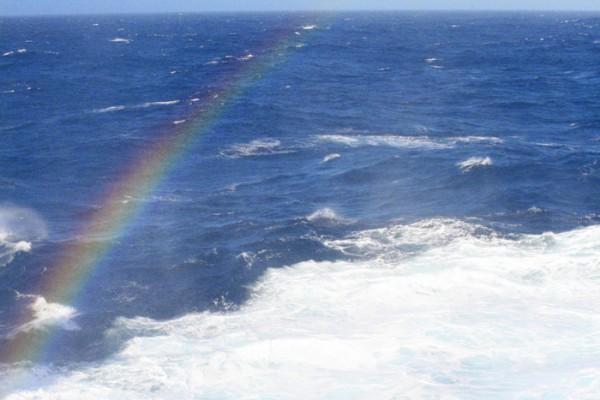 Ein Regenbogen in der Gischt einer Welle